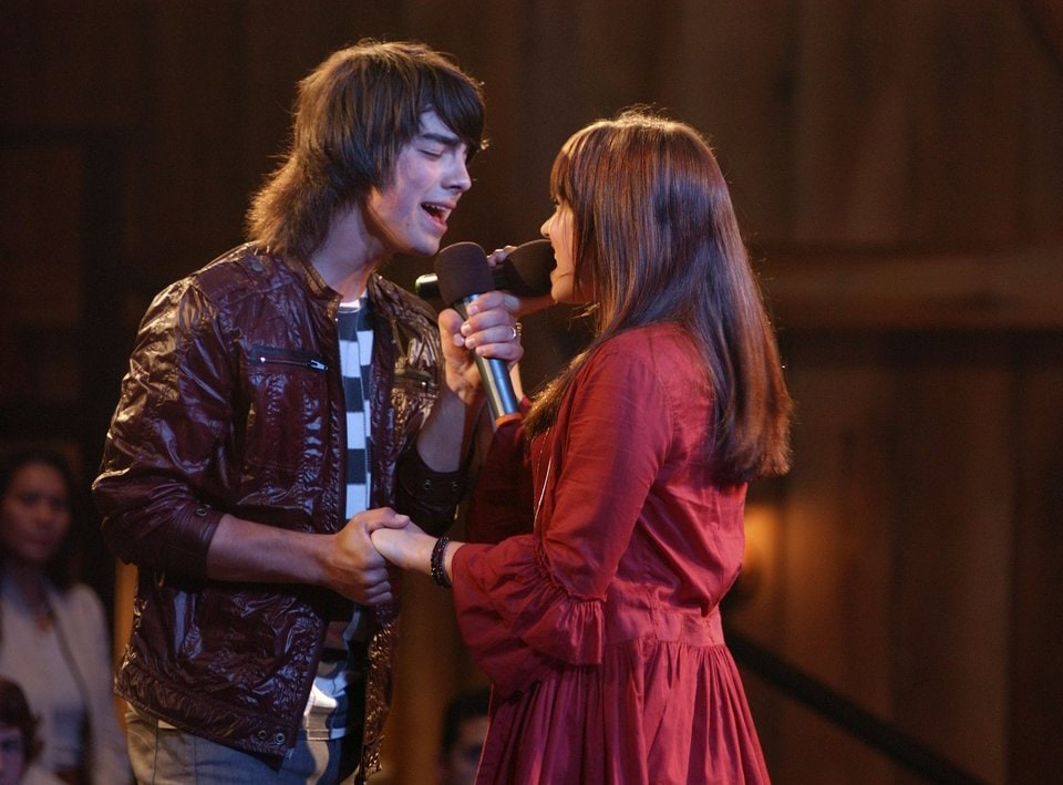 """CAMP ROCK - """"Camp Rock,"""" a music-filled Disney Channel Original Movie, features the Jonas Brothers as members of a leading musical group, Connect 3. When member Shane Gray (Joe Jonas) needs to counter his bad boy rocker image, he is sent by his fellow band members Nate (Nick Jonas) and Jason (Kevin Jonas) to the music camp as a guest instructor. There he meets camper Mitchie Torres (Demi Lovato), a teen girl with an extraordinary voice and a driving ambition to be a pop singer but unfortunately she can only spend her summer at the expensive camp by helping her mom work in the mess hall between classes. When Shane overhears Mitchie singing from behind closed doors, he sets out to find the girl with the beautiful voice, on """"Camp Rock,"""" FRIDAY, JUNE 20 (8:00 P.M., ET/PT) on Disney Channel. (DISNEY CHANNEL/JOHN MEDLAND) JOE JONAS, DEMI LOVATO"""