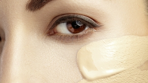 Beautiful face of young woman with cosmetic foundation on a skin. Beauty treatment concept.