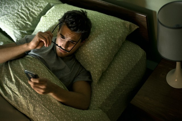 Man checking cell phone in bed