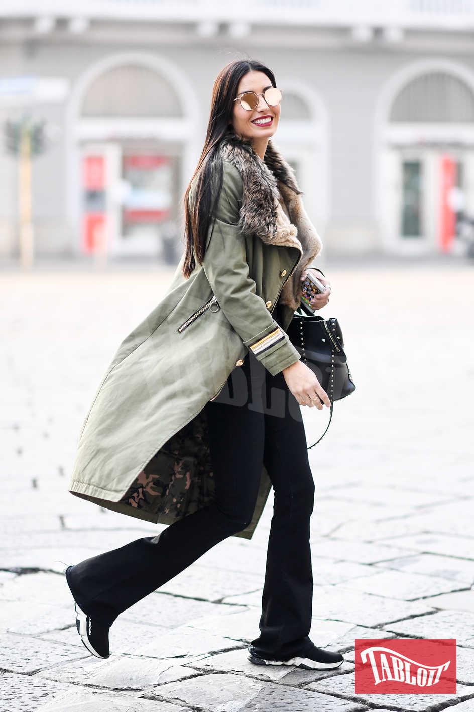 Elisabetta Gregoraci ha scelto un look sportivo: pantaloni neri della tuta, scarpe da ginnastica in tinta, occhiali a specchio e cappotto con pelo. Il tocco chic? La borsa nera con borchie firmata Valentino