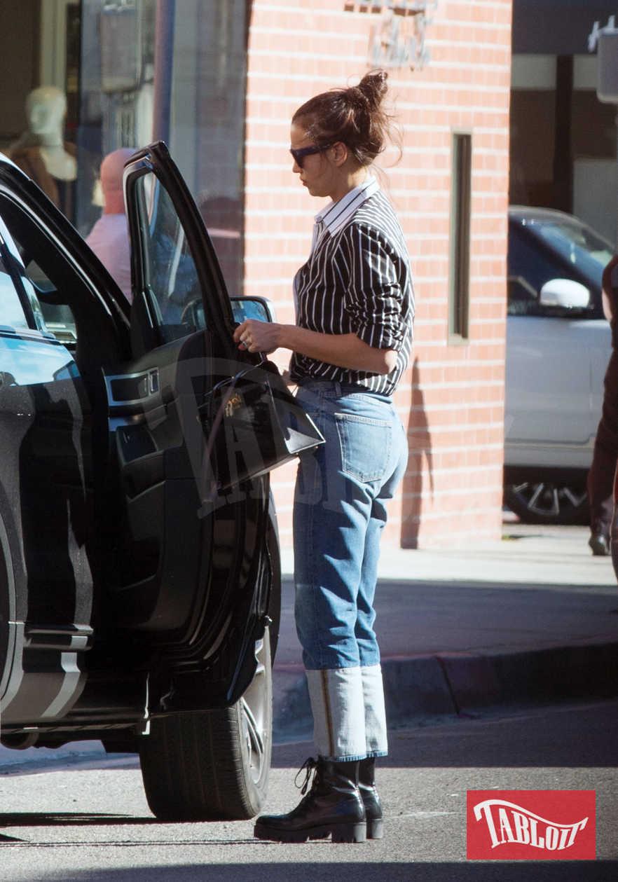 Irina Shayk ha scelto un outfit sportivo: camicia a righe, jeans e scarponcini neri