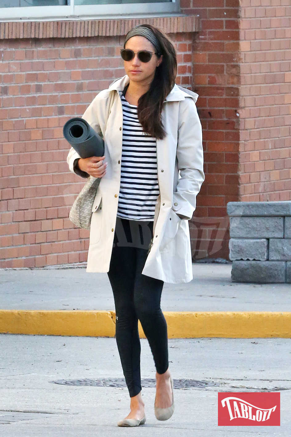 """Meghan paparazzata per le vie di Toronto, Canada, lo scorso aprile. Sottobraccio l'immancabile tappetino per fare yoga. La fidanzata di Harry ha annunciato la sua intenzione di lasciare la serie tv """"Suits"""" (e probabilmente la carriera di attrice)"""