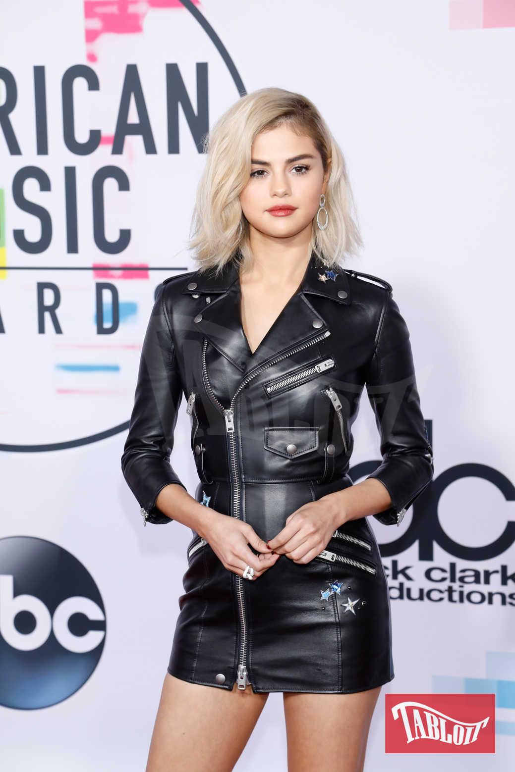 """Selena Gomez agli American Music Awards ha sfoggiato un mini abito in pelle stile """"chiodo"""" firmato Coach. La cantante, con capelli biondissimi, ha dato una svolta rock al suo stile"""