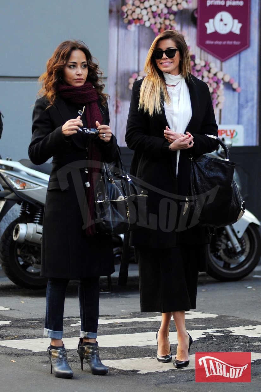Aida in centro a Milano con un'amica. Occhialoni scuri, cappotto nero, camicia bianca con sciarpa abbinata e pantaloni a palazzo neri a vita alta. Tocco glam: il tacco a spillo
