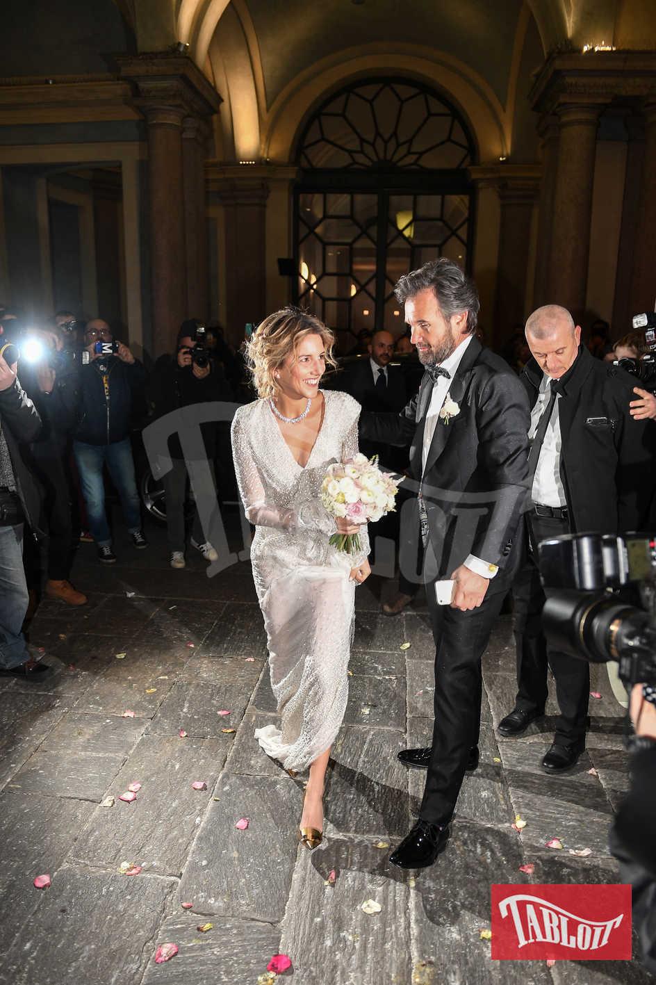 Elegantissimi gli sposi: lui in smoking nero con papillon, lei con abito avorio ricoperto da strass dalla scollatura a V