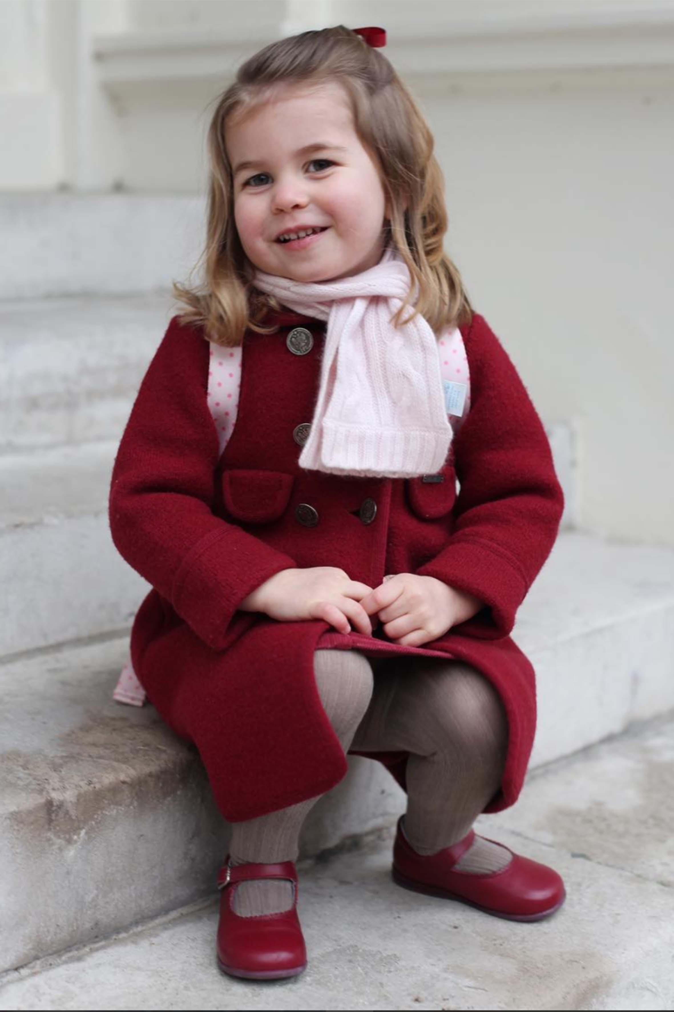 Sorridente e molto somigliante alla nonna Elisabetta, Charlotte per il suo primo giorno di scuola indossa un cappotto rosso scuro del valore di 120 sterline di Amaia Kids. A completare il look una sciarpa rosa e uno zaino pony Cath Kidston