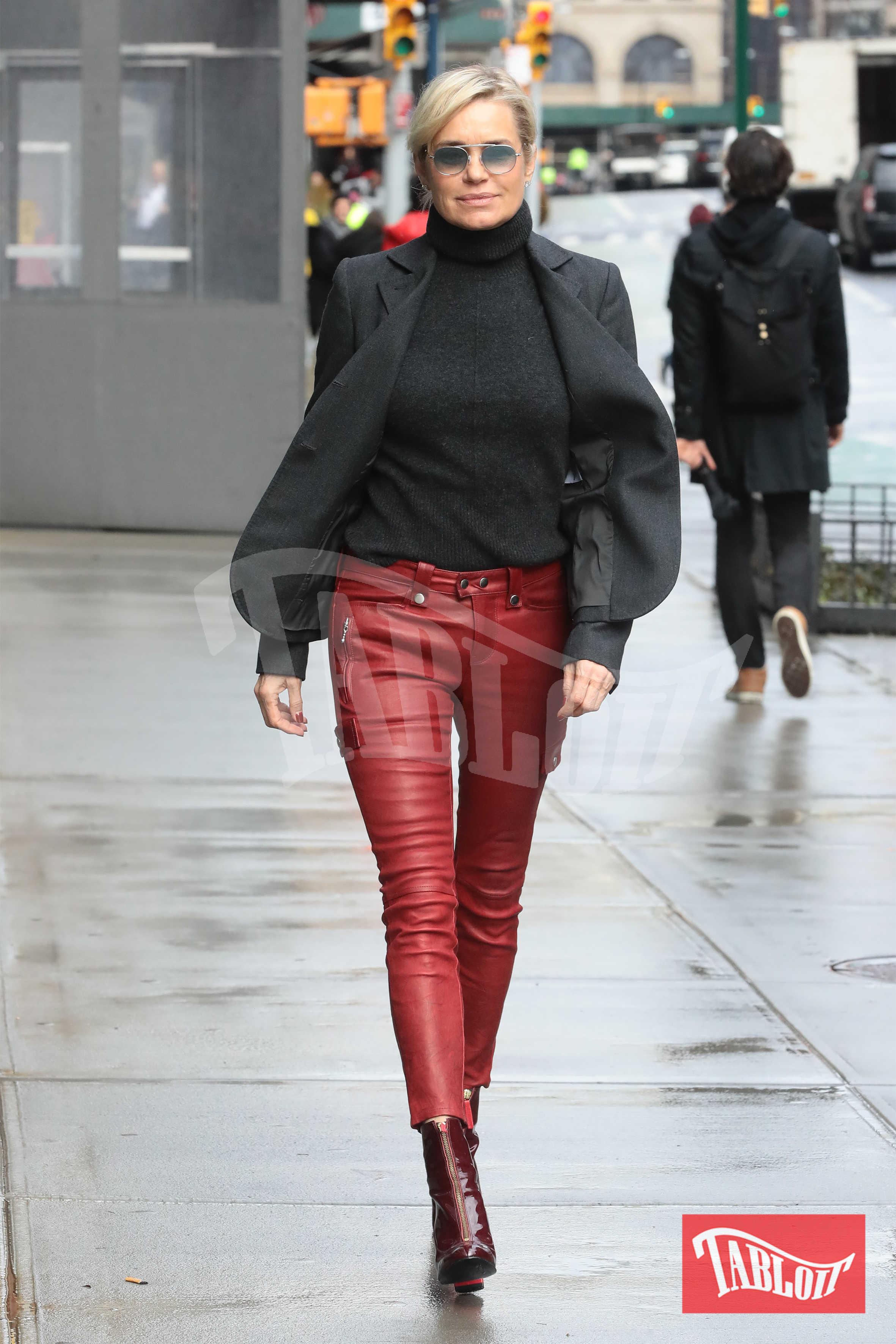 Yolanda Hadid a New York City sfoggia un look che mixa rock e chic: giacca grigia abbinata al dolcevita, pantaloni rossi in pelle e stivaletti in tinta. Occhiali fumè per completare il look