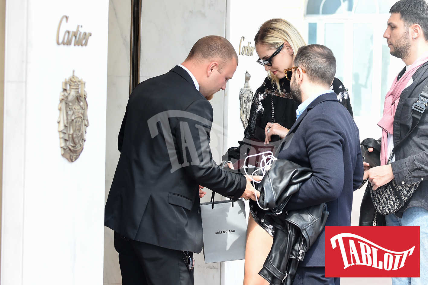 Un addetto alla sicurezza controlla la borsa di Chiara prima dell'ingresso nel negozio di Cartier